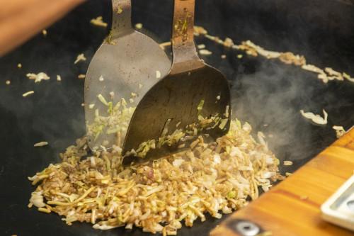 熱々の鉄板の上で、手際よく炒めていく